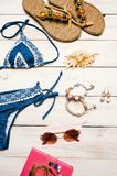 Flat lay of summer fashion with blue bikini swimsuit camera and other girl accessories on white wooden background.  Stock Photography