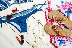 Flat lay of summer fashion with blue bikini swimsuit camera and other girl accessories on white wooden background.  Royalty Free Stock Photography