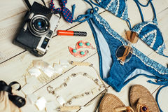 Flat lay of summer fashion with blue bikini swimsuit, camera and other girl accessories on white wooden  background.  Stock Photo