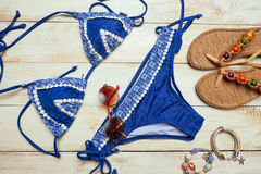 Flat lay of summer fashion with blue bikini swimsuit, and girl accessories on white wooden  background.  Stock Photography
