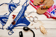 Flat lay of summer fashion with blue bikini swimsuit, and girl accessories on white wooden  background.  Royalty Free Stock Photo