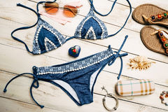 Flat lay of summer fashion with blue bikini swimsuit, and girl accessories on white wooden  background.  Royalty Free Stock Image