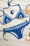 Flat lay of summer fashion with blue bikini swimsuit, and girl accessories on white wooden  background.  Royalty Free Stock Photos
