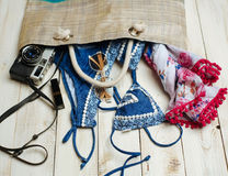 Flat lay of summer fashion with blue bikini swimsuit inside the bag, and other girl accessories on white wooden  background Royalty Free Stock Images