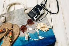 Flat lay of summer fashion with camera, slippers, sunglasses and other girl accessories on top of the bag on white wooden backgrou Royalty Free Stock Photography
