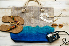 Flat lay of summer fashion with camera, slippers, sunglasses and other girl accessories on top of the bag on white wooden backgrou Stock Images