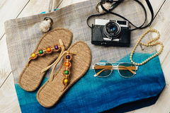 Flat lay of summer fashion with camera, slippers, sunglasses and other girl accessories on top of the bag on white wooden backgrou Stock Image