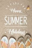 Flat lay with summer flip flops and seashell on sand with 'Happy summer holiday ' lettering stock photos