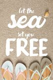 Flat lay with summer flip flops and seashell on sand, let sea set you free inscription stock photography