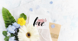 Flat lay summer flowers mock up with greeting card on craft pape Royalty Free Stock Image