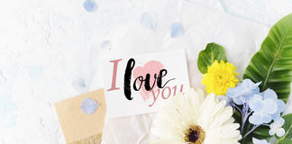 Flat lay summer flowers mock up with greeting card on craft pape Royalty Free Stock Photos