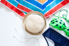 Flat lay of summer items, colorful umbrella, hat and swimsuit Royalty Free Stock Photo