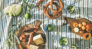 Picnic set with fruit, cheese, toast, honey, wine with a wicker basket and a blanket. Beautiful summer background with stock image