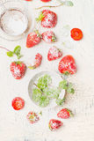 Flat lay of summer Strawberries  , bowl with mint and sugar on light vintage background Stock Photo