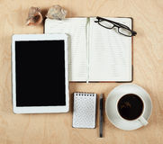 Flat lay of tablet computer, notebook, coffee cup  and pencil with blank center on wood background, top view Royalty Free Stock Photo