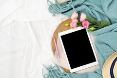 Flat lay tablet and flowers on white blanket with turquoise plaid. Window light, space for text blog, posts Stock Image