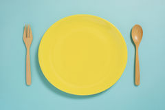 Flat lay of tableware, yellow plate and fork on pastel blue colo. R background Stock Photography