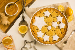 Flat lay tart with lemon, orange and ginger jam decorated with star-shaped cookies. Flat lay tart with lemon and orange, ginger jam decorated with star-shaped Stock Photos