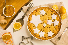 Flat lay tart with lemon, orange and ginger jam decorated with star-shaped cookies. Flat lay tart with lemon and orange, ginger jam decorated with star-shaped Royalty Free Stock Image