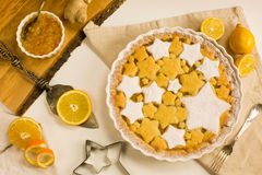 Flat lay tart with lemon, orange and ginger jam decorated with star-shaped cookies. Flat lay tart with lemon and orange, ginger jam decorated with star-shaped Royalty Free Stock Photography
