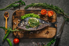Flat lay of tasty dorado fish with vegetables and spices Stock Photo