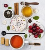 Flat lay with tea donut honey cherry spoon breakfast composition on white table top view stock photography