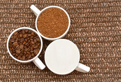 Flat lay. Three white cups with coffee, beans and sugar Royalty Free Stock Photos
