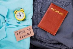 Flat lay time to travel concept. Male clothes, alarm clock and passport. Close up, top view Royalty Free Stock Photo
