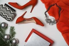 Flat lay to new year and christmas party outfit composition red shoes accessories jewelry clutch fir tree with balls white. Top view to new year and christmas royalty free stock photography