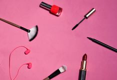 Flat lay the tools to create makeup on pink background royalty free stock photography