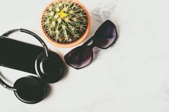 Flat lay, top view of cactus, mobile phone, sun glasses and audio headphones over marbe background with copy space stock images
