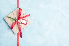 Flat lay top view christmas gift box wrapped in craft paper with red ribbon on light blue background Stock Photos