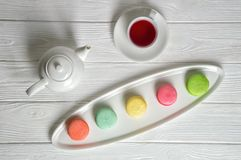 Flat lay, top view. Close up. Provence breakfast. Colorful pastry macarons laid out on an oblong plate, a cup of berry tea.