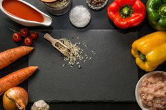 Flat lay, top view. Close up. Ingredients for baking stuffed bell peppers lined around a black stone cutting board. Copy space