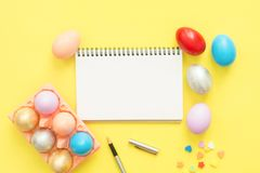 Flat lay top view colorful easter egg painted in pastel colors composition and mock up blank notebook with paint brush. Flat lay top view colorful easter egg Stock Photos