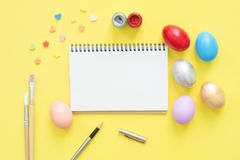 Flat lay top view colorful easter egg painted in pastel colors composition and mock up blank notebook with paint brush. Flat lay top view colorful easter egg Royalty Free Stock Photo