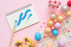 Flat lay top view colorful easter egg painted in pastel colors composition and spring flowers with paint brush notebook. Flat lay top view colorful easter egg Royalty Free Stock Image
