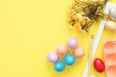 Flat lay top view colorful easter egg painted in pastel colors composition and spring flowers with paint brush on yellow pastel. Flat lay top view colorful Stock Photography