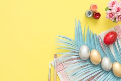 Flat lay top view colorful easter egg painted in pastel colors composition and spring flowers with paint brush. Flat lay top view colorful easter egg painted in Royalty Free Stock Photography