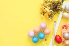 Flat lay top view colorful easter egg painted in pastel colors composition and spring flowers with paint brush on yellow pastel co. Lor background. Easter day Stock Images