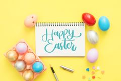 Flat lay top view colorful easter egg painted in pastel colors composition and text Happy Easter Day on notebook with paint brush. Flat lay top view colorful Stock Photography