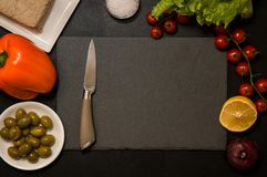 Flat lay. Italian food. Kitchen knife and black cutting board surrounded by plant based ingredients. Copy space stock photography