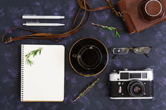 Flat lay, top view office table desk. Desk workspace with retro camera, diary, pen, glasses, case, cup of coffee, rosemary on dark Royalty Free Stock Photos