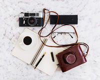 Flat lay, top view office table desk. Desk workspace with retro camera, diary, pen, glasses, case, cup of coffee on white backgrou Royalty Free Stock Photography