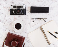 Flat lay, top view office table desk. Desk workspace with retro camera, diary, pen, glasses, case, cup of coffee on white backgrou Royalty Free Stock Images