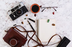 Flat lay, top view office table desk. Desk workspace with retro camera, diary, pen, glasses, case, cup of coffee on white backgrou Stock Image