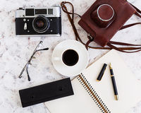 Flat lay, top view office table desk. Desk workspace with retro camera, diary, pen, glasses, case, cup of coffee on white backgrou Royalty Free Stock Photos
