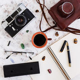 Flat lay, top view office table desk. Desk workspace with retro camera, diary, pen, glasses, case, cup of coffee on white backgrou Royalty Free Stock Photo