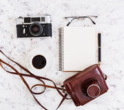 Flat lay, top view office table desk. Desk workspace with retro camera, diary, pen, glasses, case, cup of coffee on white backgrou Stock Images