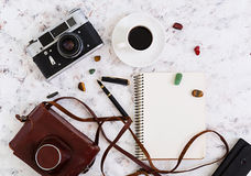 Flat lay, top view office table desk. Desk workspace with retro camera, diary, pen, glasses, case, cup of coffee on white backgrou Stock Photography